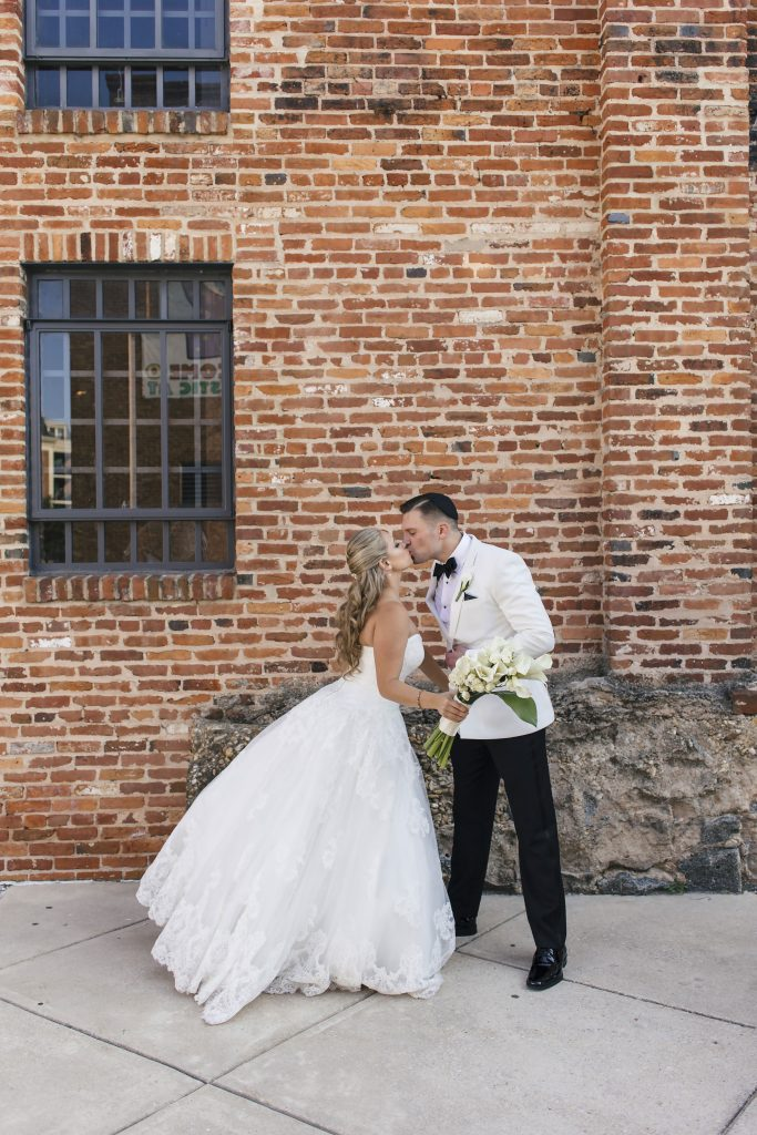 Bride and Groom Kissing Outside of the American Visionary Arts Museum. Howerton+Wooten Events.